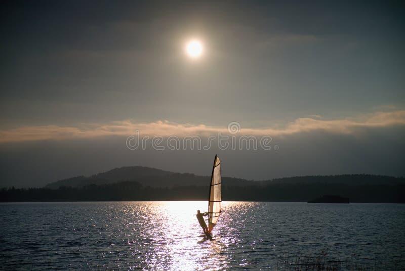 风帆冲浪者航行到微风里射击了与柔和的过滤器 强的太阳做反射 库存图片