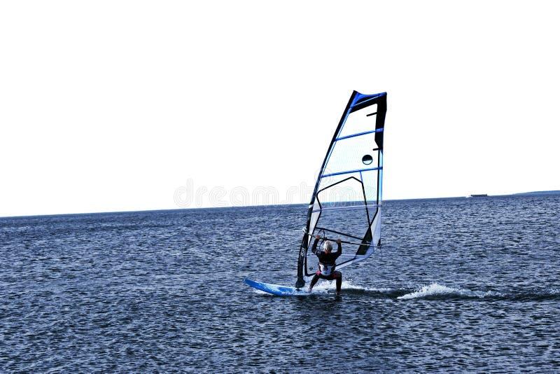 风帆冲浪者迅速滑动在蓝色海 E 免版税图库摄影