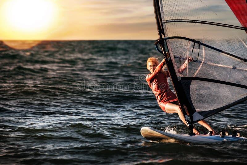 风帆冲浪,乐趣在海洋,极端体育 妇女生活方式 免版税图库摄影