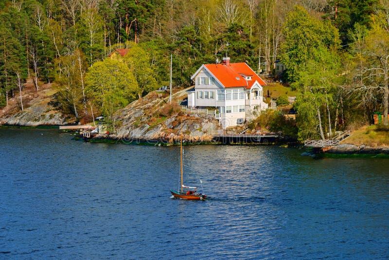风帆游艇通过进行中在著名白色新艺术主义别墅被设计的Folkvang前面建筑师Folke Zetterwall  免版税库存照片