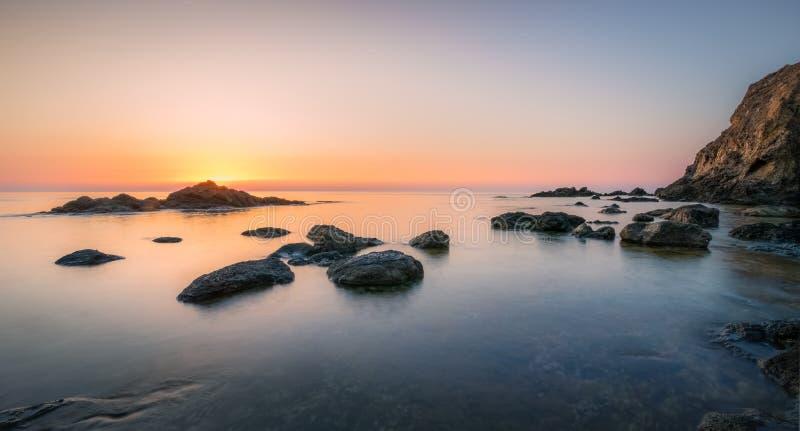 风平浪静沐浴的岩石 免版税库存照片