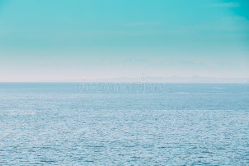 风平浪静海洋和蓝色清楚的天空背景 轻轻地蓝色颜色 库存图片