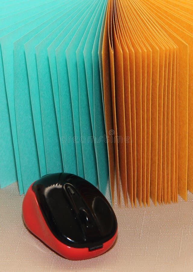 风扇打开的纸张背景上的鼠标,记录蓝色和黄色 免版税图库摄影