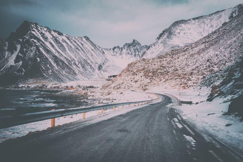 风景冬天路通过对村庄Vikten大西洋岸的,罗弗敦群岛,挪威的多雪的落矶山脉 免版税库存图片