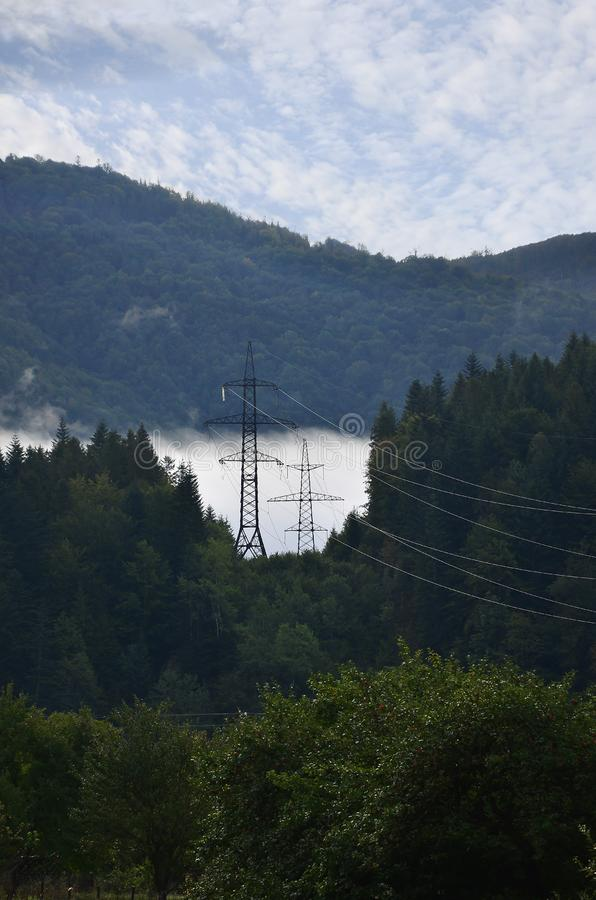 风景在一个山区 与输电线的塔在山 免版税库存照片