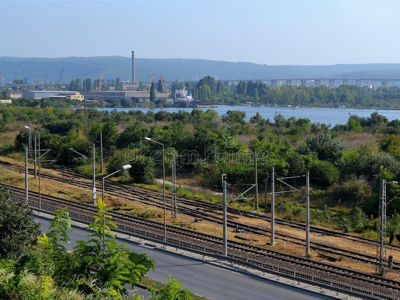 风景在夏天晴天:高速公路运行沿铁路,工厂厂房的,起重机和绿色木头在湖支持 免版税库存图片