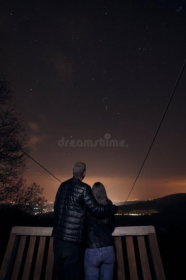 风景射击,担任主角在夜间的星的年轻夫妇,在自然原野 天体摄影 免版税库存图片