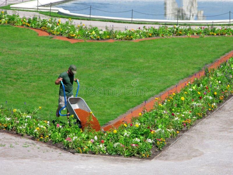 风景工作在城市公园,有庭院独轮车的工作员 免版税库存照片