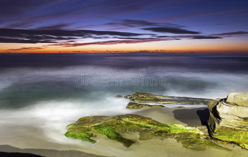 风景日落和剧烈的天空颜色在Windansea海滩拉霍亚加利福尼亚 库存照片