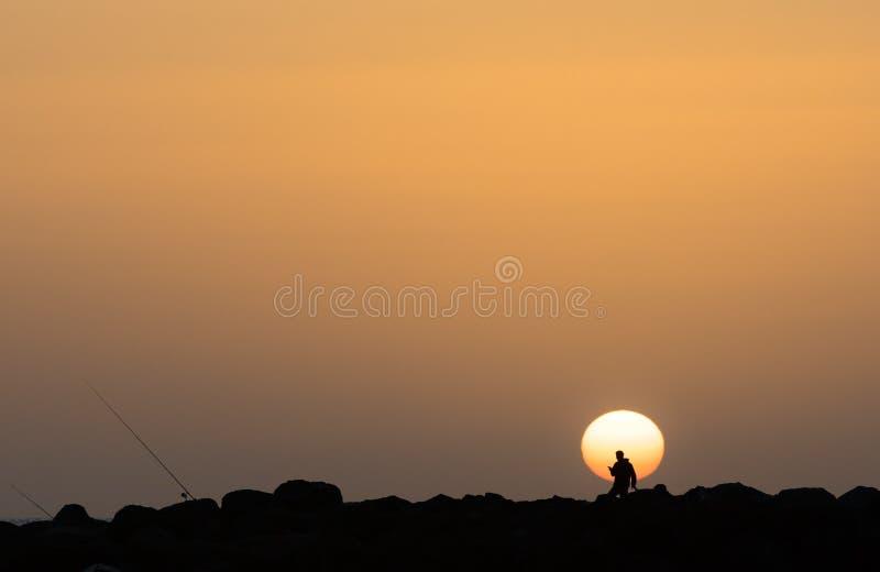 风景日落,检查他的电话,大加那利岛海岛的一个人的剪影在西班牙 免版税库存图片