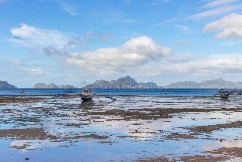 风景热带风景 在海滨的低潮 与传统philippinian渔船的全景海景 免版税库存照片