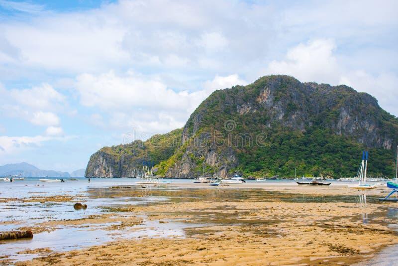 风景热带风景 在海滨的低潮 与山和传统philippinian渔船的海景 免版税库存照片
