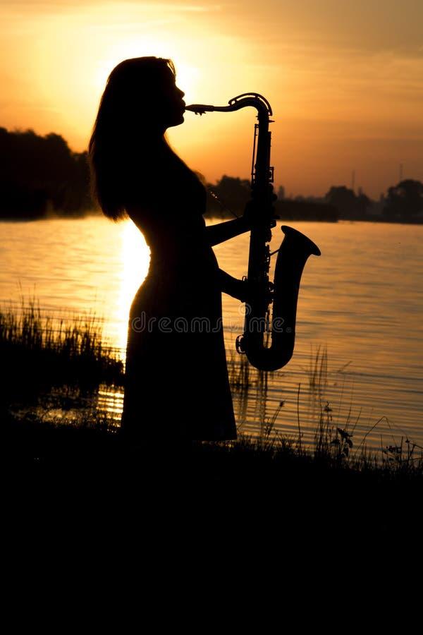 风景的黎明的背景的女孩在河的河岸的 库存图片