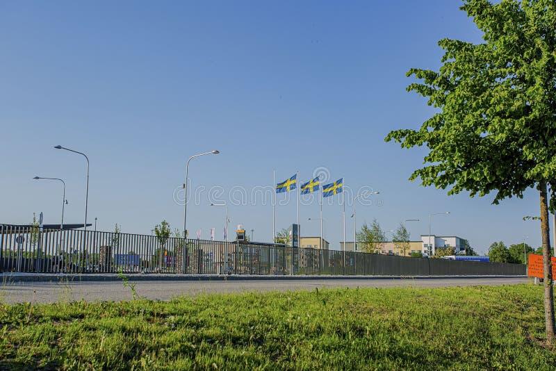 风景看法与金属篱芭和三面瑞典旗子的 美好的地标背景 图库摄影