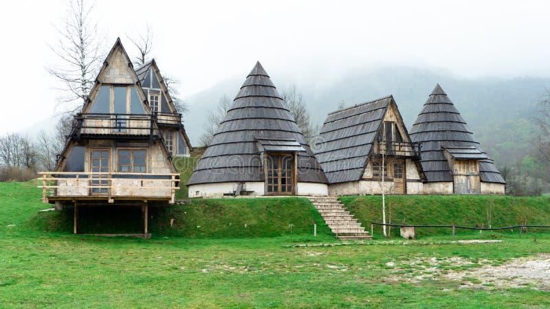 风景雾在路一边的芒廷村 有针对性的屋顶和绿草的黑山小镇 库存图片