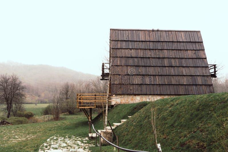 风景雾在路一边的芒廷村 有针对性的屋顶和绿草的黑山小镇 图库摄影