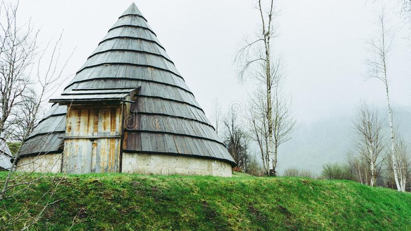 风景雾在路一边的芒廷村 有针对性的屋顶和绿草的黑山小镇 免版税图库摄影