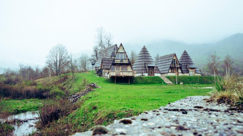 风景雾在路一边的芒廷村 有针对性的屋顶和绿草的黑山小镇 库存照片