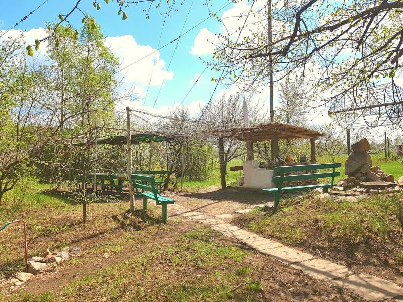 风景 在蓝天下,长木凳 委员会木机盖以屋顶的形式 石头 在树和绿色附近 免版税库存图片