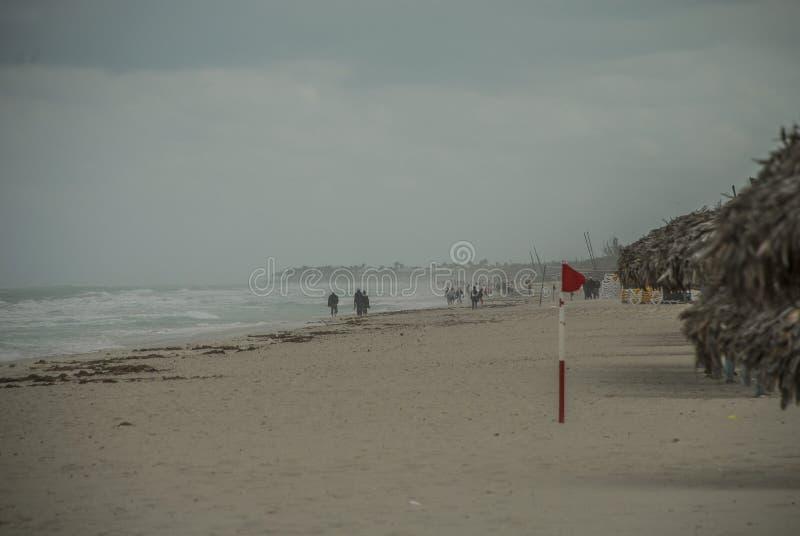 风暴在海洋张贴了在海滩的一面红旗 免版税库存图片