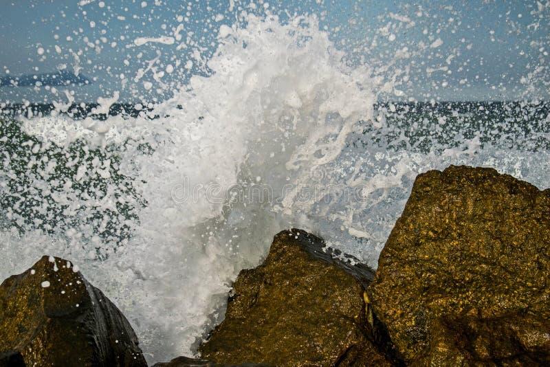 风暴海上开始 波浪击中岩石,并且驱散水 用乌云盖的天空 免版税库存照片