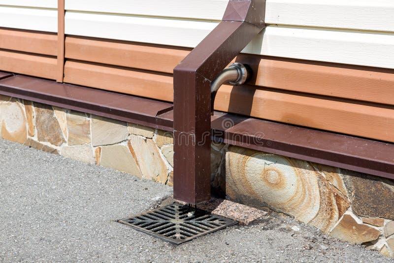 风暴系统雨水从屋顶的排水管 库存照片