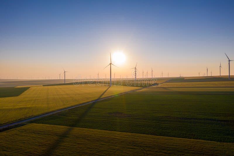 风的发电器鸟瞰图在一块美好的麦田的 风的涡轮农场 风轮机剪影 绕环投球法涡轮 ?? 库存图片