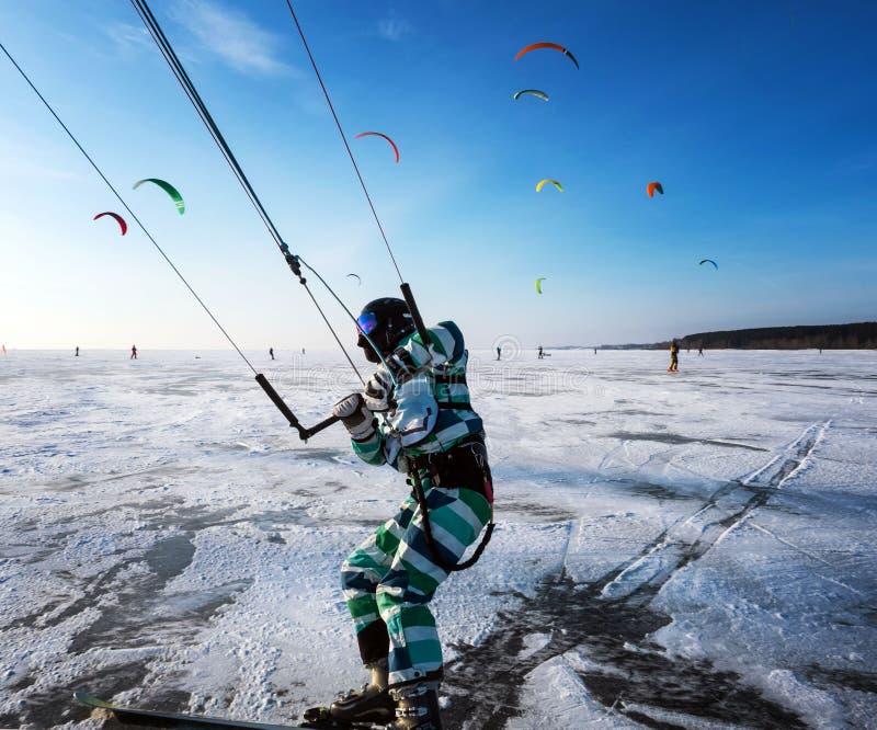 风筝海运冲浪 年轻人,在风帆下的kiing的滑雪在山的一个冻湖 库存照片