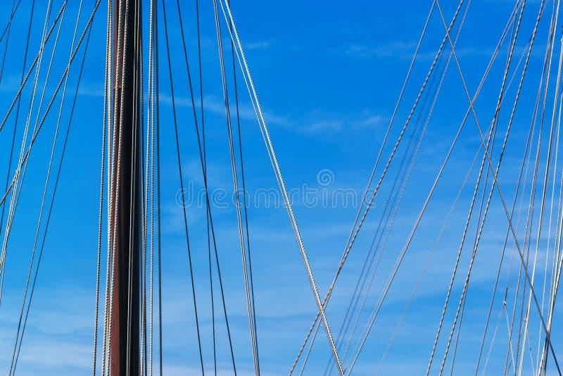 风船帆柱和绳索在反对蓝天的港口 库存图片