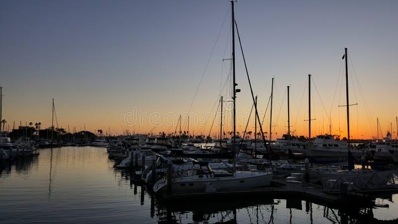 风船被束缚在小游艇船坞船坞在日落在圣迭戈加利福尼亚 库存照片