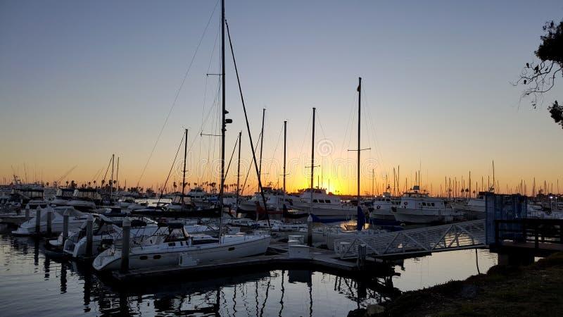 风船被束缚在小游艇船坞船坞在日落在圣迭戈加利福尼亚 免版税图库摄影