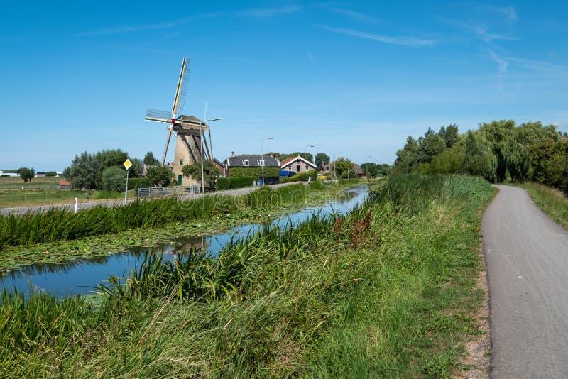 风车和农场沿运河在堤在Maasland附近, N 免版税库存照片
