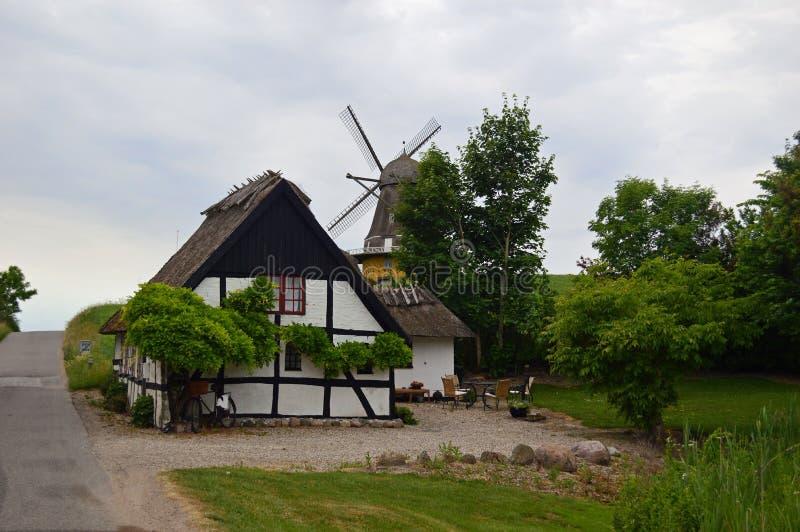 风车和农舍在乡下在北部西兰,丹麦 免版税库存照片