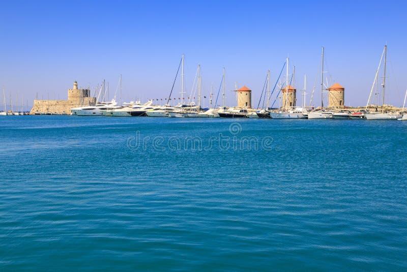 风车和圣尼古拉斯塔和灯塔在Mandraki口岸 库存照片