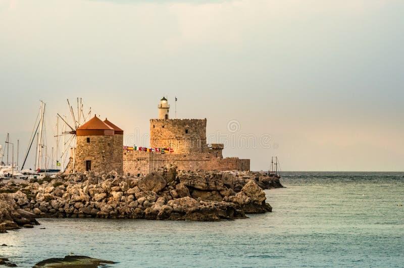 风车和灯塔在Mandraki港口,罗得岛,希腊 库存照片