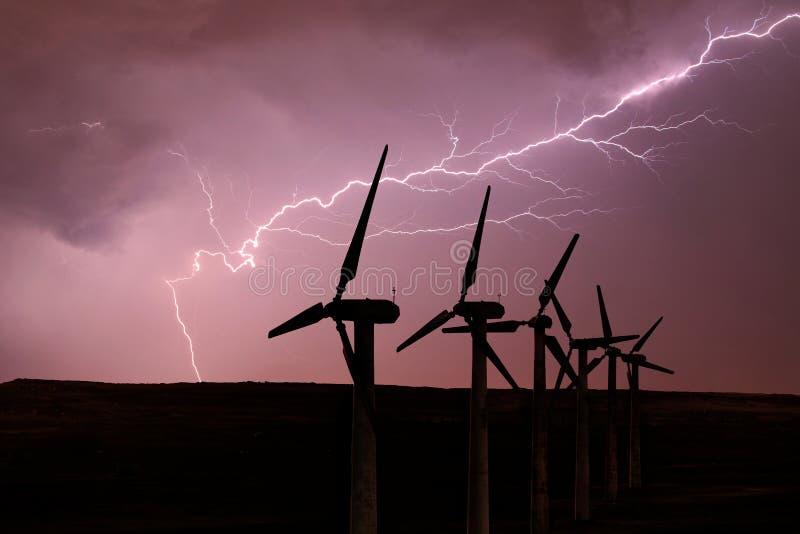 风轮机剪影在风雨如磐的天空的背景的 免版税库存图片