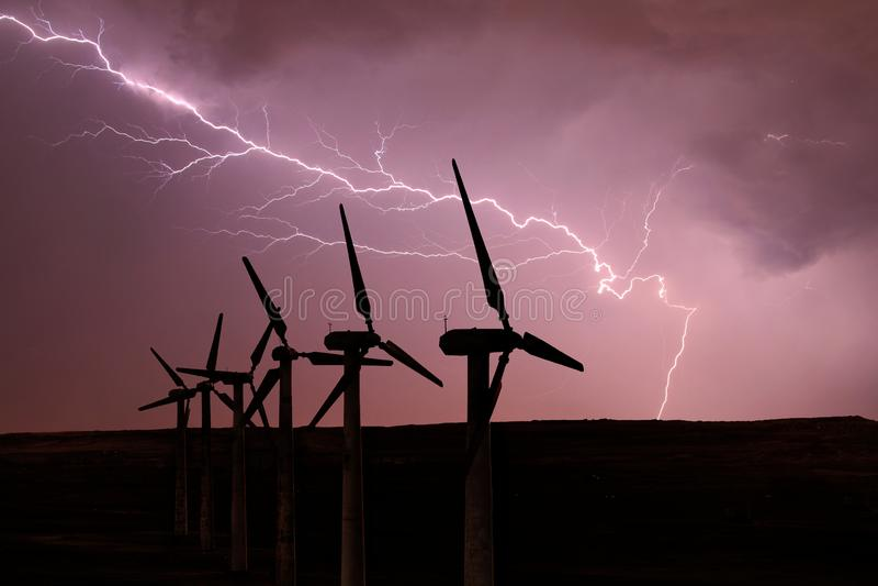 风轮机剪影在风雨如磐的天空的背景的 库存图片
