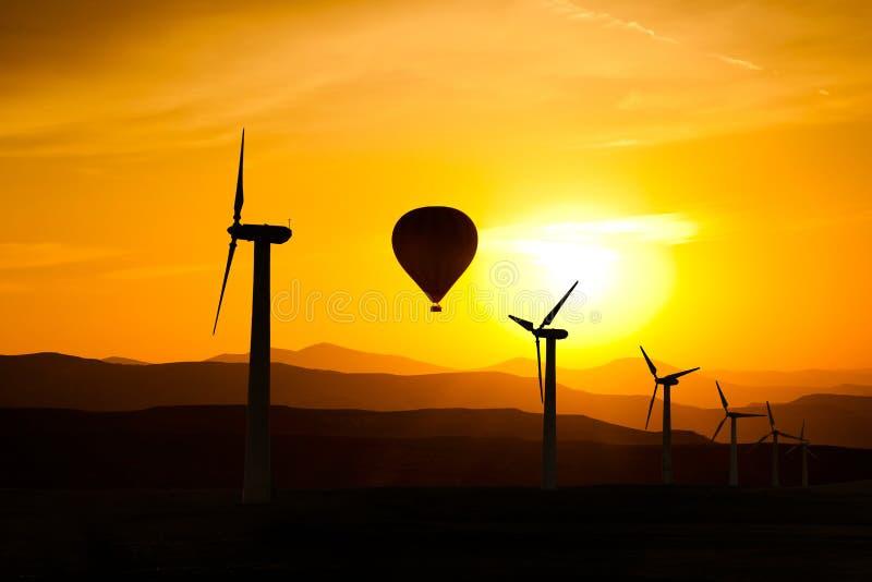 风轮机和一个热空气气球剪影在山背景  库存图片