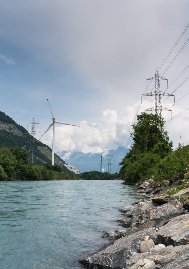 风轮机和输电线在一条河的河岸山谷的 免版税库存图片