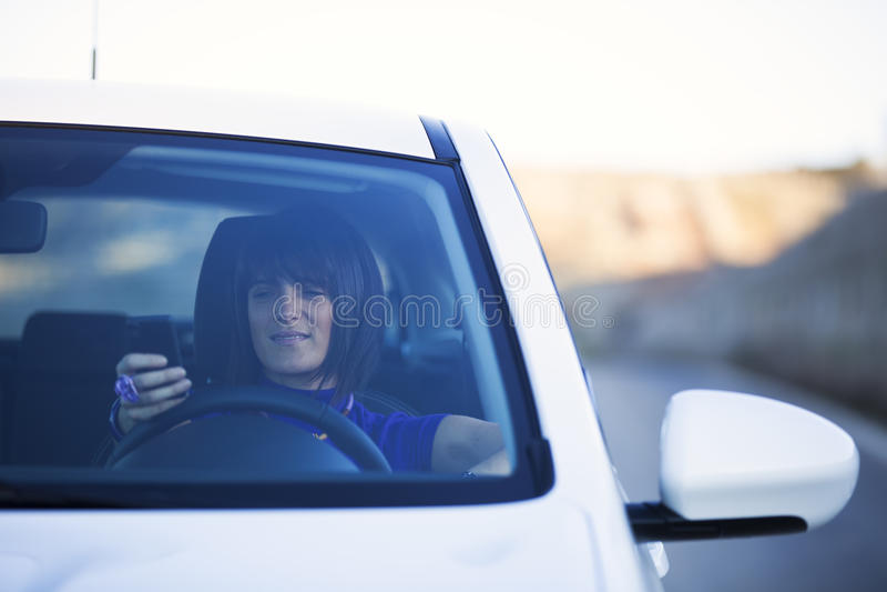 驾驶的妇女拿着手机 库存照片