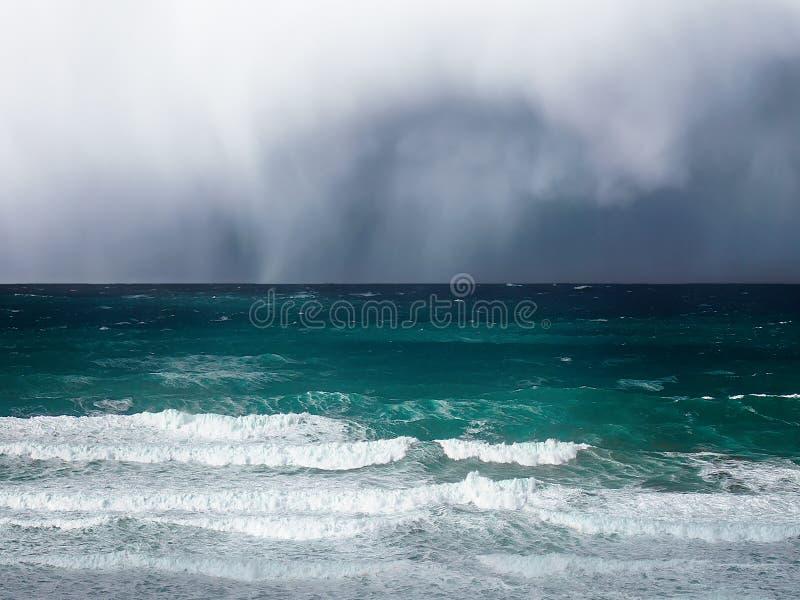 风雨如磐的云彩和雨在海 免版税库存照片