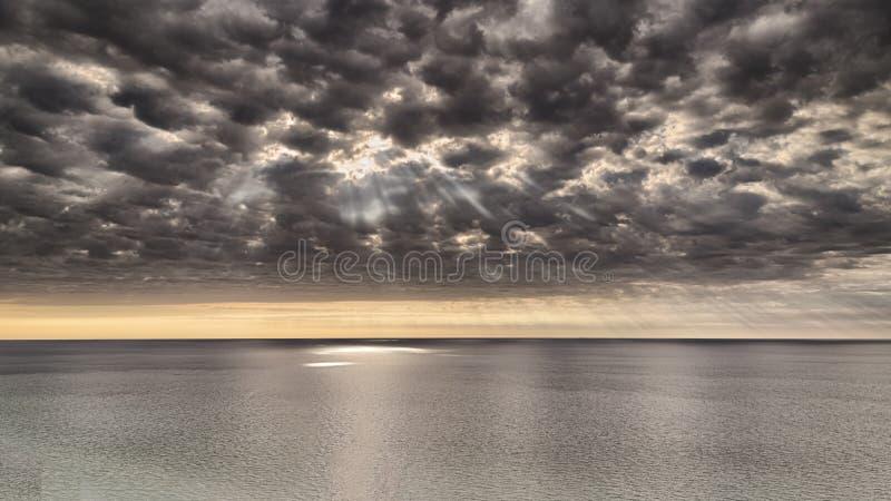 风雨如磐的剧烈的云彩和太阳光芒在湖 库存照片
