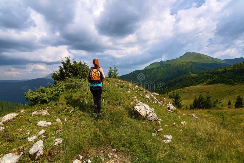 风雨如磐,象打雷天空 与山峰顶的看法  运动的红色头发女孩上升由与岩石的小山决定 极其体育运动 库存图片