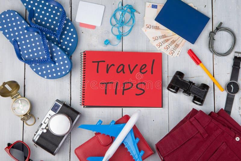 飞机、护照、金钱、照相机、指南针、笔记本有文本的& x22; 旅行tips& x22; 双筒望远镜,牛仔裤,手表,触发器,钱包 库存图片