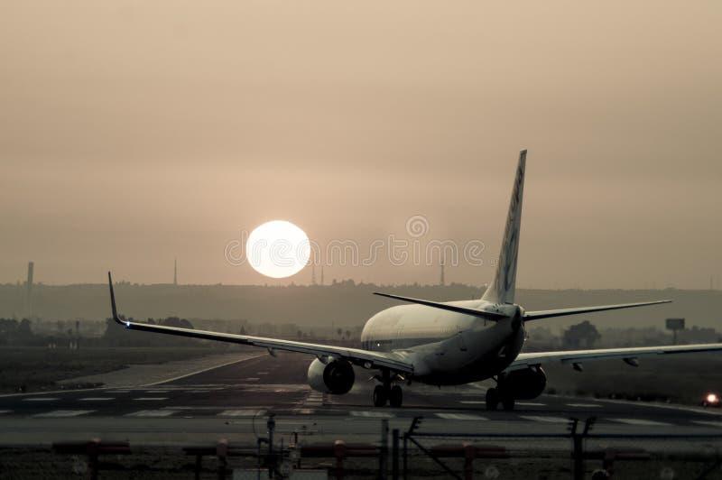 飞机从后面着陆拍摄了在塞维利亚机场在日落 免版税库存照片