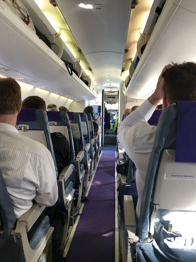 飞机内部有乘客的等待的位子的离开 免版税库存照片