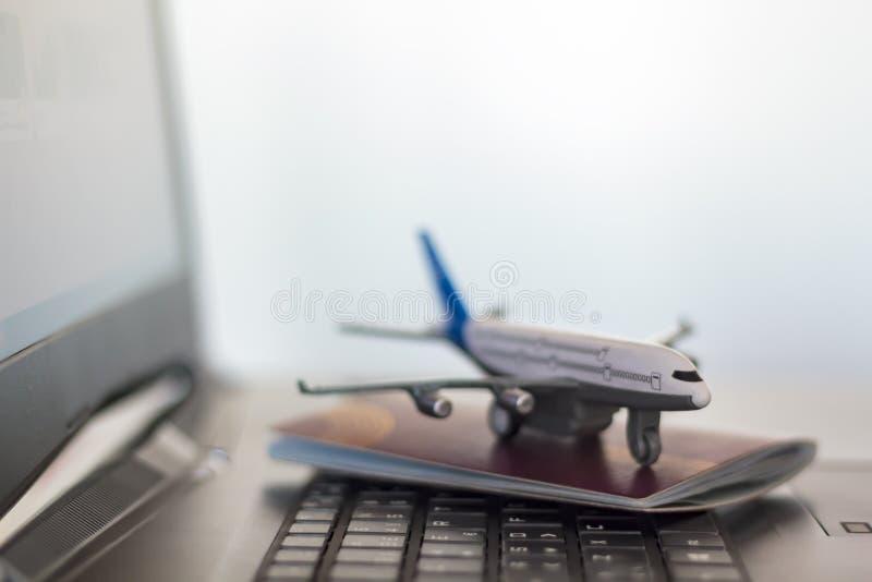 飞机和护照在膝上型计算机 免版税库存图片