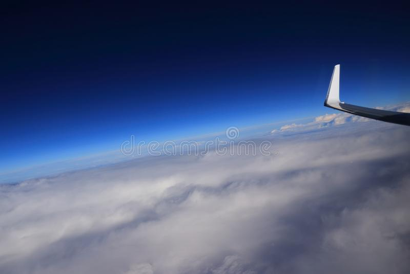 飞机在云彩蓝天上的翼梢飞行 库存图片