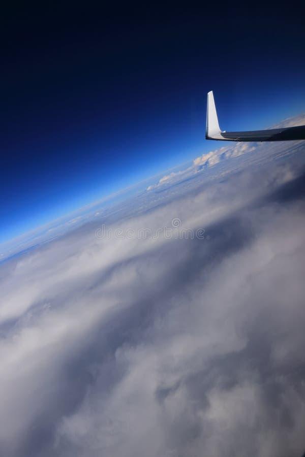 飞机在云彩蓝天上的翼梢 库存图片