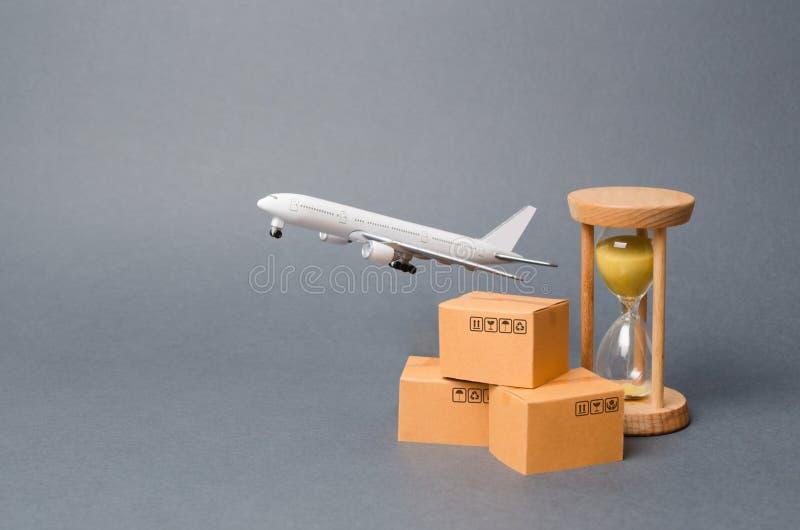 飞机在堆纸板箱和沙子时钟后离开 空运货物和小包,航寄的概念 r 免版税库存图片